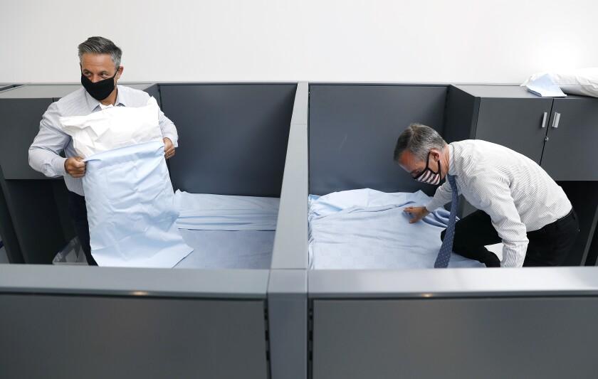 Councilman Joe Buscaino, left, and Mayor Eric Garcetti make beds at a transitional housing facility