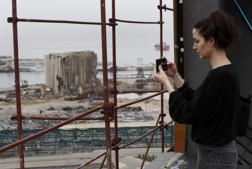 Joana Dagher, 33, who lost her memory for two full months from the trauma she suffered in the massive August explosion at the Beirut port, including a cerebral contusion and brain lesions, takes pictures of the explosion scene from her damaged apartment rooftop, in Beirut, Lebanon, Wednesday, Jan. 27, 2021. The mental health impact of the Beirut explosion that killed more than 200 and wounded more than 6,000 continues to lay its heavy weight on those who managed to survive the day. (AP Photo/Hussein Malla)