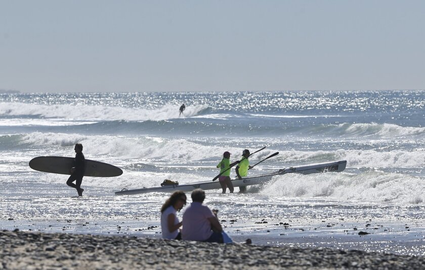 Surfers and kayakers share the beach as they enjoy the unusually warm temperatures Tuesday, Feb. 16, 2016, in Encinitas, Calif.  California is having another day of unseasonable warmth before a low-pressure system brings rain and snow. (AP Photo/Lenny Ignelzi)