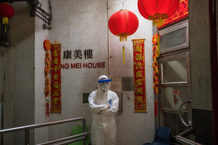 An official in protective gear stand guard outside the Hong Mei House in Hong Kong.