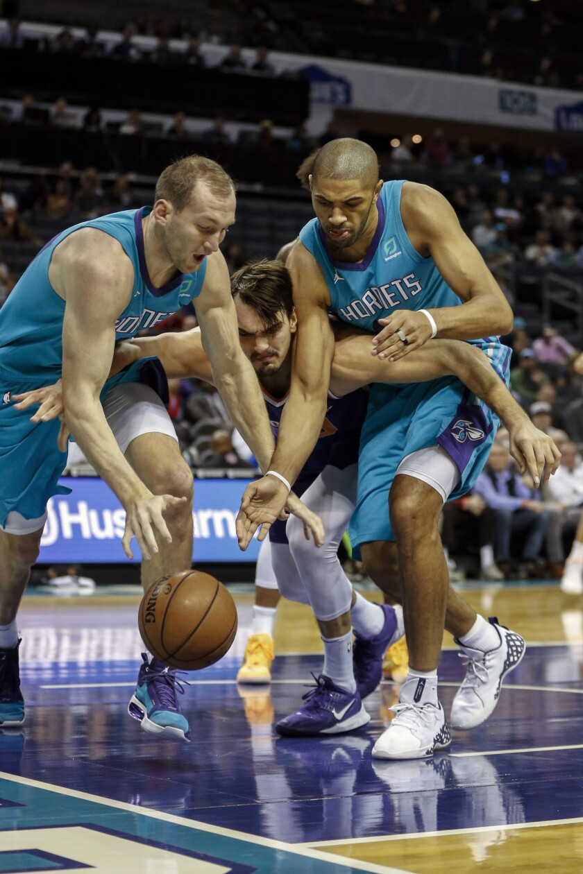 Phoenix Suns forward Dario Saric, center, battles Charlotte Hornets forward Cody Zeller, left, and guard Nicolas Batum (5) in the first half of an NBA basketball game in Charlotte, N.C., Monday, Dec. 2, 2019. (AP Photo/Nell Redmond)