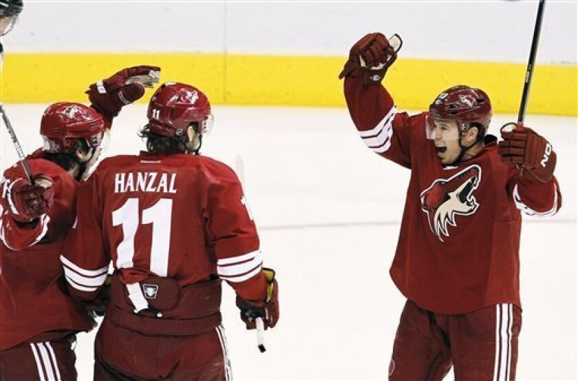 Phoenix Coyotes' Ray Whitney, right, celebrates his 1,000th career point on an assist with Antoine Vermette, left, and Martin Hanzal (11), of the Czech Republic, during the second period in an NHL hockey game against the Anaheim Ducks, Saturday, March 31, 2012, in Glendale, Ariz. (AP Photo/Ross D.