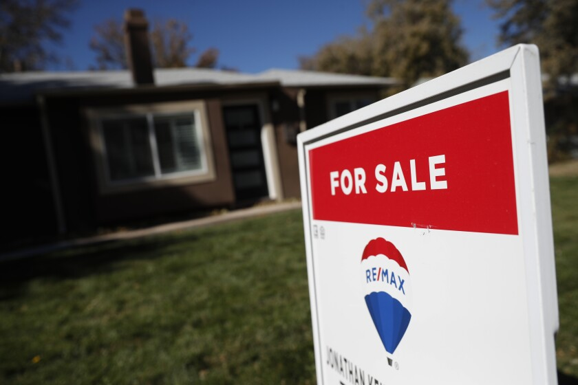 In this Oct. 22, 2019 file photo, a sign stands outside a home for sale in southeast Denver.