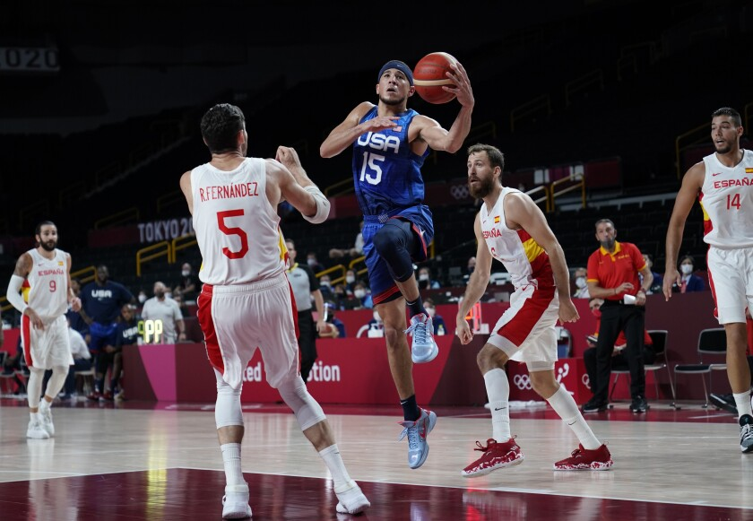 U.S. basketball player Devin Booker leaps in front of Spain's Rudy Fernandez at the Tokyo Olympics.