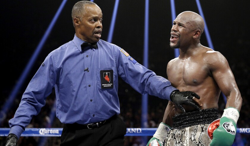 Referee Kenny Bayless holds back Floyd Mayweather during his welterweight title fight against Marcos Maidana on Sept. 13, 2014.