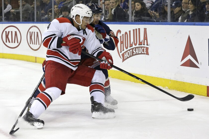 Carolina Hurricanes defenseman Andrej Sekera fights for the pucks with New York forward Mats Zuccarello during a game on Jan. 31.