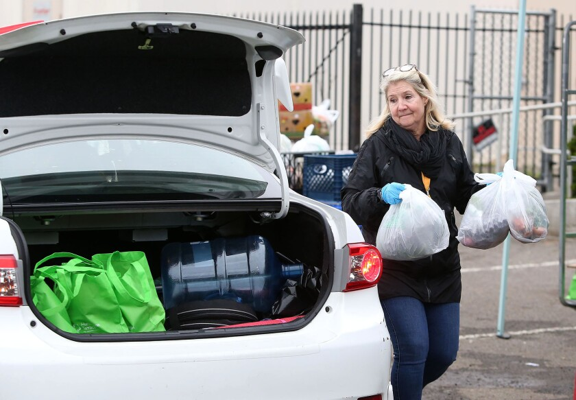 Volunteer Lesli Henderson carries bags of groceries to a waiting car outside the Laguna Food Pantry on Wednesday as visitors received goods through drive-up distribution.