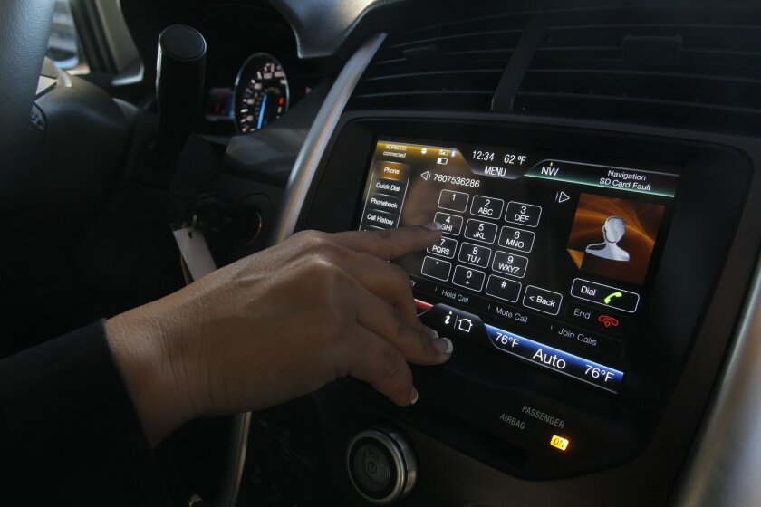 Ford's Sync system melds the smart phone with dashboard controls. Automakers are working to bring more mobile applications to vehicles in a safe manner