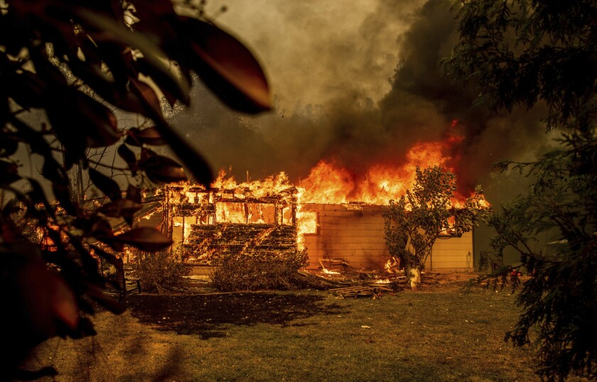 Flames consume a house near Old Oregon Trail as the Fawn Fire burns north of Redding in Shasta County, Calif., on Thursday, Sept. 23, 2021. (AP Photo/Ethan Swope)