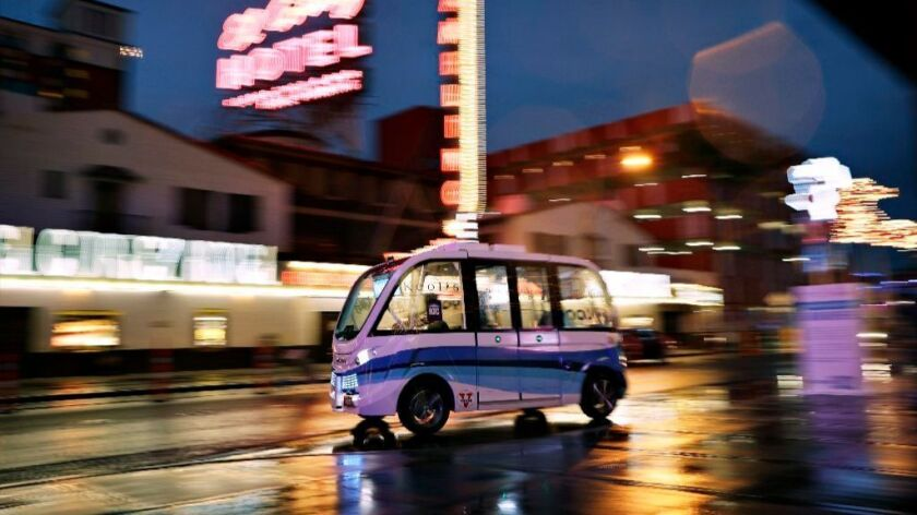 A driverless electric shuttle has begun carrying passengers in a test program in a downtown Las Vegas entertainment district.