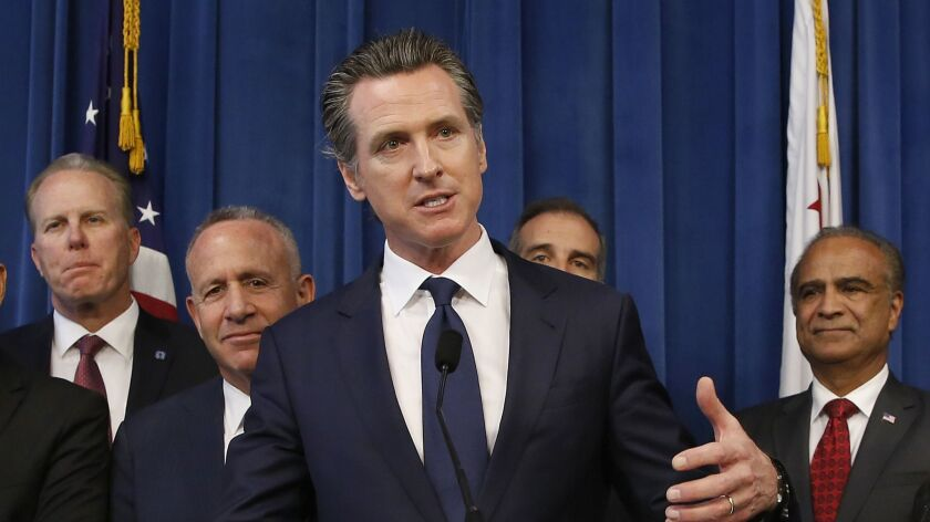 Gov. Gavin Newsom, center, discusses the homeless problem facing California after a meeting in Sacramento in March with the mayors of some of the state's largest cities.