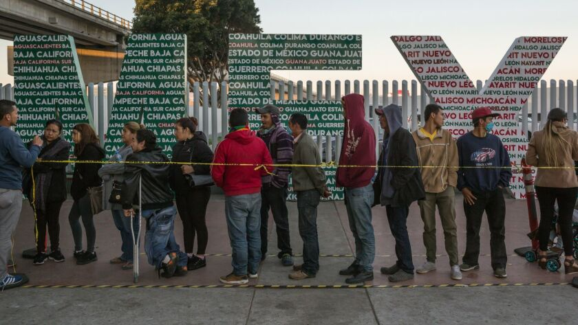 "Migrants line up to get their names on ""La Lista"" at the El Chapparal border crossing in Tijuana, Mexico."