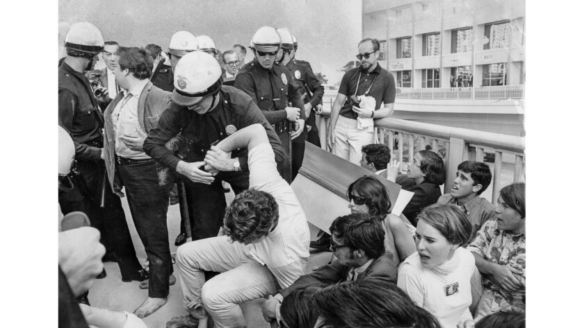 June 23, 1967: A policeman grasps the arm of a man who refused to leave the area in front of Century