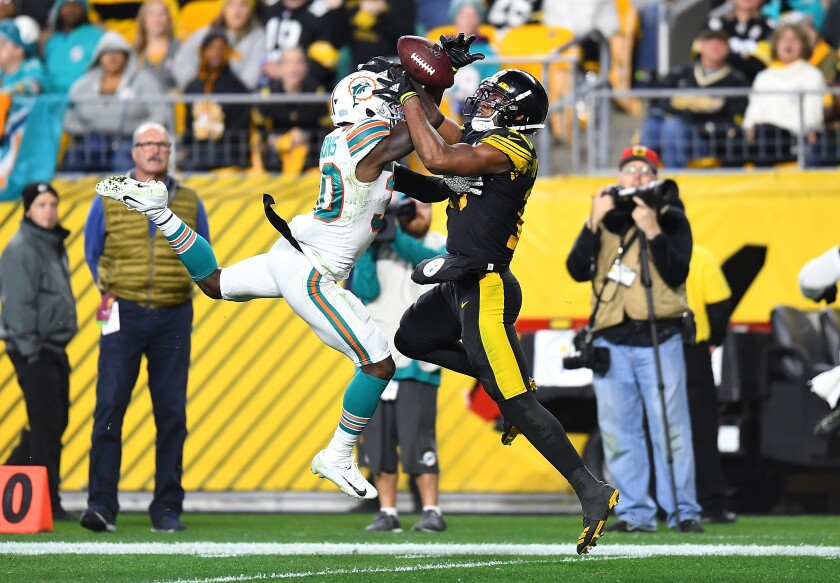 Pittsburgh Steelers wide receiver JuJu Smith-Schuster catches a pass in front of Miami Dolphins safety Chris Lammons.