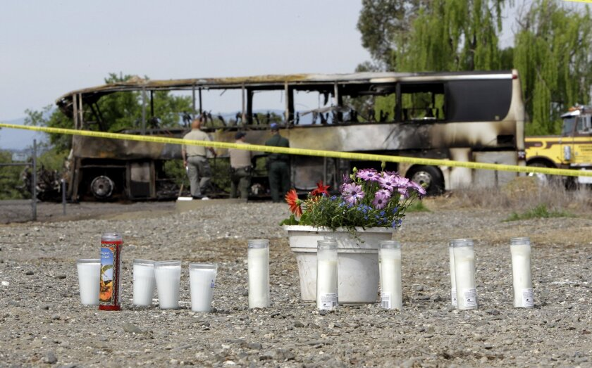 Candles and flowers are displayed at a makeshift memorial for the victims of a multi-vehicle accident that included a tour bus and a FedEX truck on Interstate 5 in Orland, Calif.