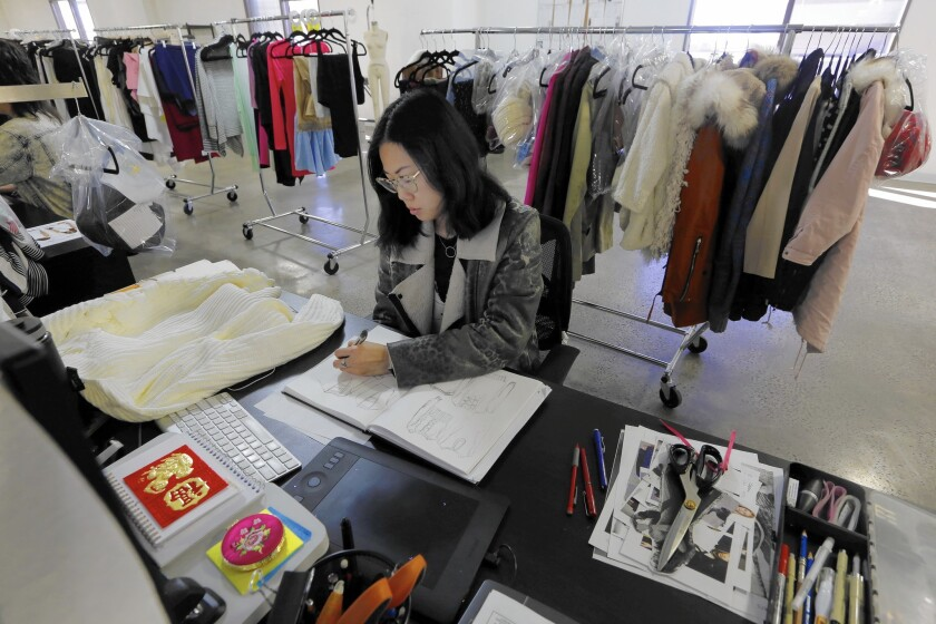 Associate designer Chrystal Lacza works on drawings at her desk at online clothing retailer Tobi in Los Angeles. This is the company's slow period because of Chinese New Year.