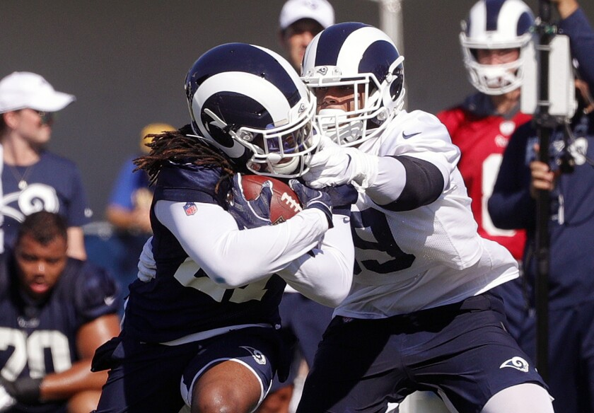 Rams running back Darrell Henderson is grabbed by the face mask by Rams defensive tackle Aaron Donald as they practice at the first day of the Los Angeles Rams training camp at UC Irvine.