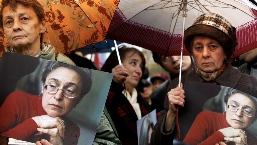 People hold portraits of Anna Politkovskaya during a rally to mark the first anniversary of the Rus