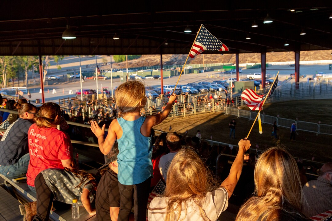 A child waves a flag with her siblings at an equestrian center.