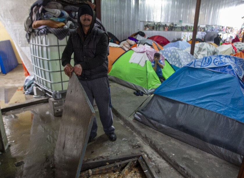 An employee at the Juventud 2000 shelter in the Zona Norte neighborhood in Tijuana shows  where raw sewage flowed in to the shelter during the morning rains on Monday.