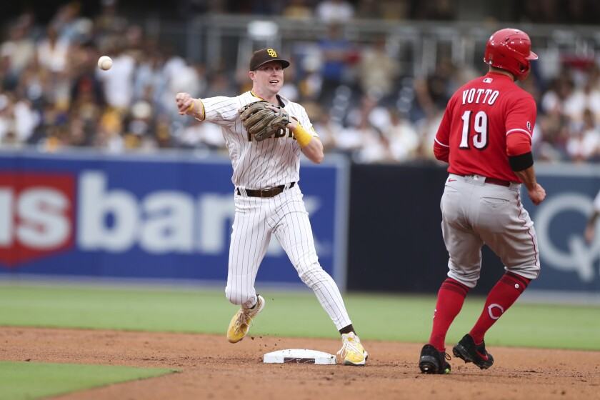 San Diego Padres second baseman Jake Cronenworth, left, throws to first base