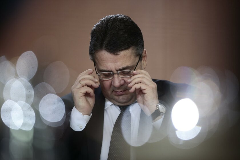German Vice Chancellor and Economy Minister Sigmar Gabriel reads in documents prior to the weekly cabinet meeting at the chancellery in Berlin, Wednesday, Jan. 28, 2015. Gabriel will present the annual German economic report with the governments economy projection later the day. The reflections in