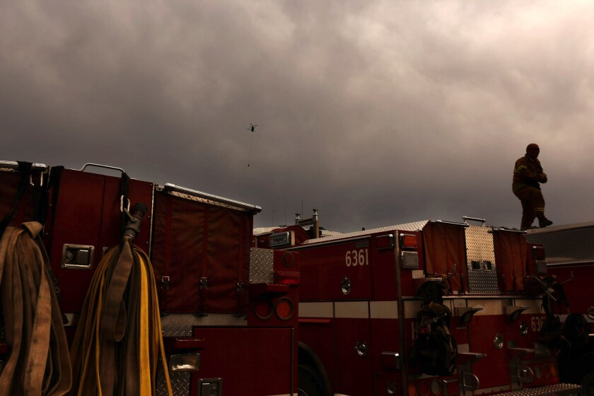 A firefighter walks on top of a fire engine as rain begins to fall in Lake County just south of Clear Lake on Tuesday.