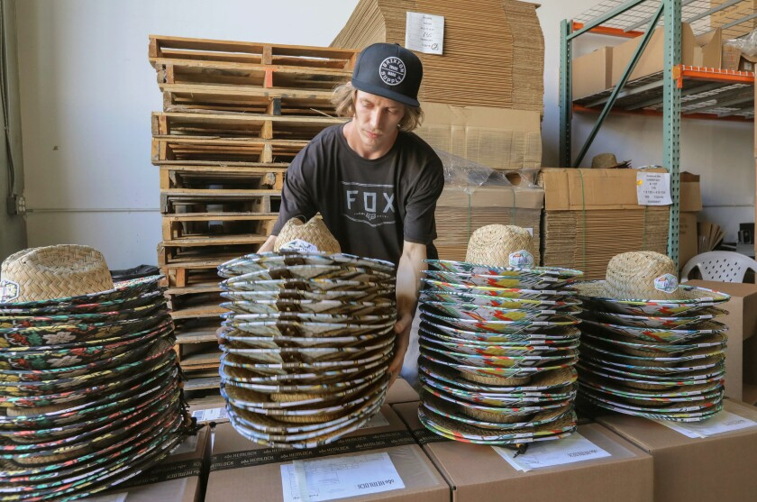 At Hemlock Hat Co. warehouse employee Randy Lawson prepares stacks of hats for shipping.