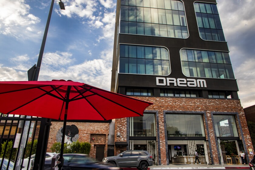 The Dream Hotel exterior and traffic and pedestrians on the street in front of it