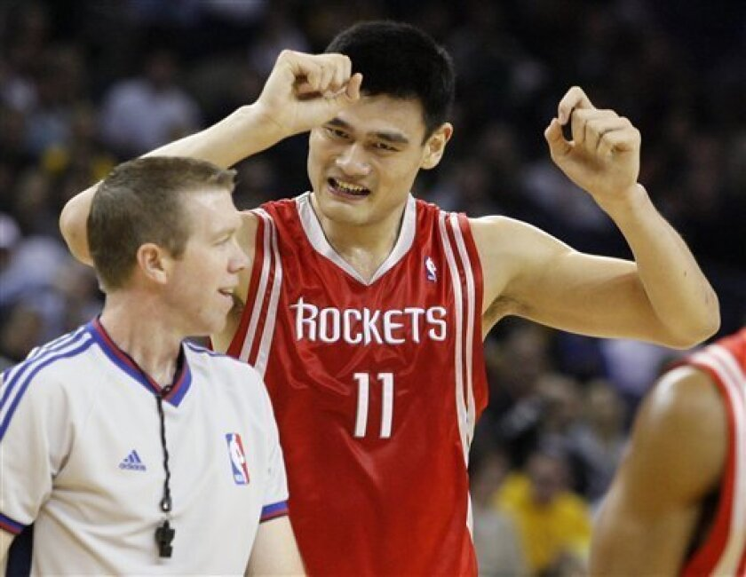 Houston Rockets' Yao Ming, of China, pleads his case to referee Ed Malloy, left, after Ming was called for a foul during the first half of an NBA basketball game against the Golden State Warriors on Friday, Dec. 12, 2008, in Oakland, Calif. (AP Photo/Ben Margot)