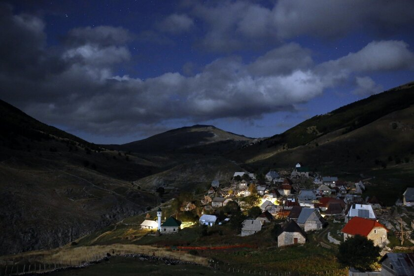 A mountain village is illuminated by moonlight as the 50 residents of village prepare to celebrate the Muslim holiday of Eid al-Adha, in the remote mountain village of Lukomir, 50 kms south of Sarajevo, on Thursday, Sept. 24, 2015. Bosnian Muslims will slaughter cattle later, with the beef and meat distributed to the needy for the holiday which honors the prophet Abraham for preparing to sacrifice his son on the order of God, who was testing his faith. (AP Photo/Amel Emric)