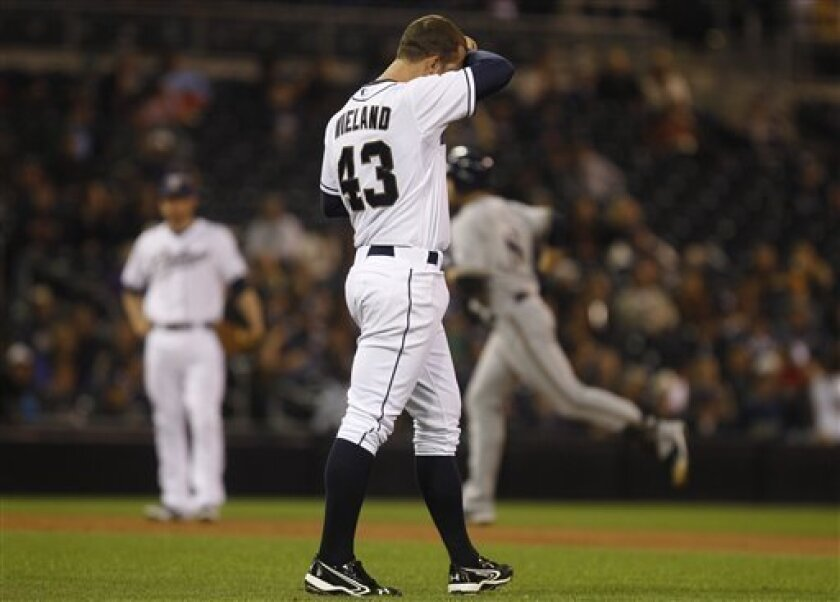 San Diego Padres pitcher Joe Wieland wipes his brow as Milwaukee Brewers' Ryan Braun rounds the bases with his second home run of the game in the fifth inning of a baseball game Monday, April 30, 2012 in San Diego. (AP Photo/Lenny Ignelzi)