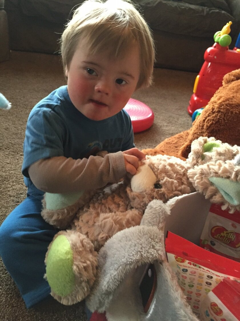 Gabriel Ford, 1, plays with toys from an Easter basket gifted to him from a neighbor after the boy's Easter eggs were stolen from his family's front lawn in Chula Vista.
