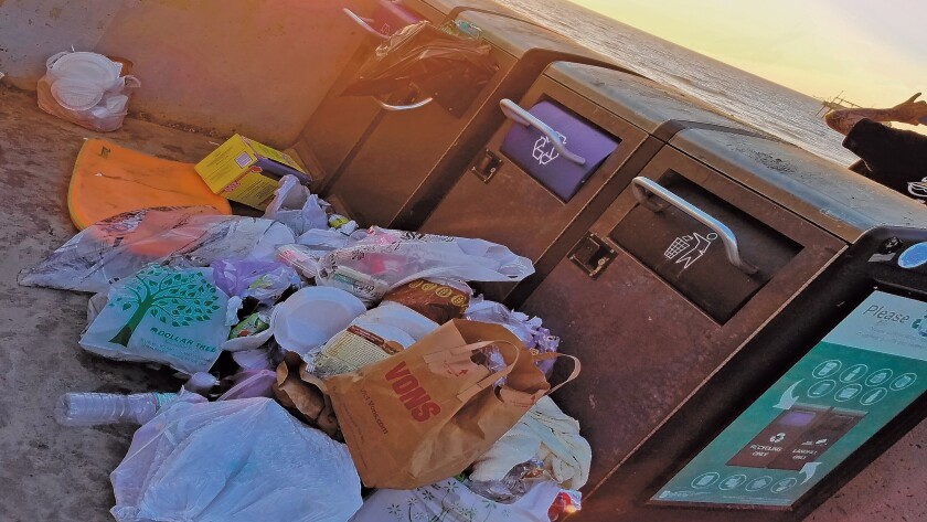 Trash is piled up in front of full trash receptacles in La Jolla Shores.