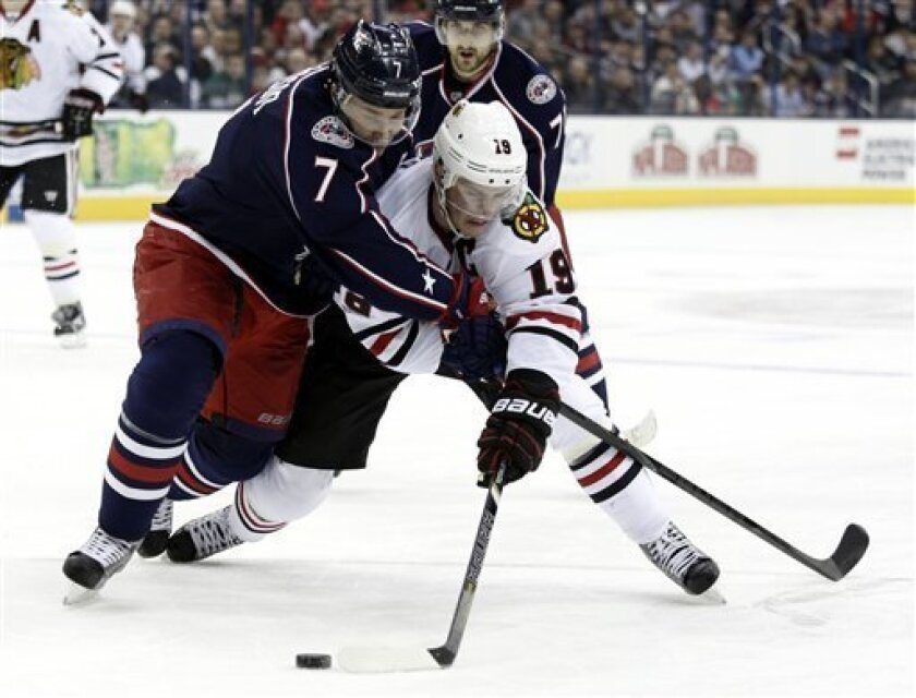 Columbus Blue Jackets' Jack Johnson, left, and Chicago Blackhawks' Jonathan Toews work for the puck during the first period of an NHL hockey game in Columbus, Ohio, Thursday, March 14, 2013. (AP Photo/Paul Vernon)