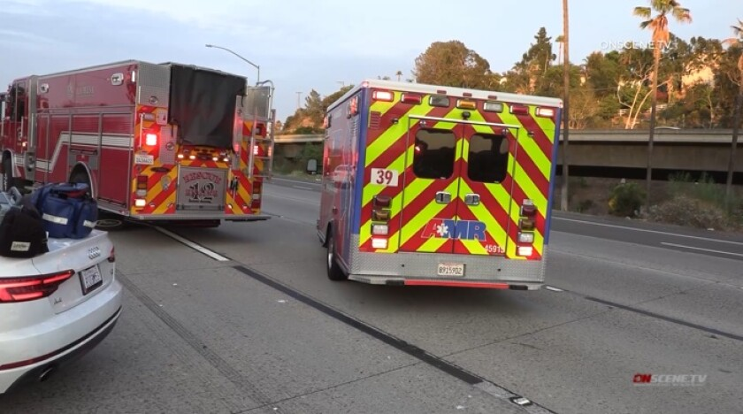 An ambulance drives away from a crash scene with a baby inside Friday night on Interstate 8 in La Mesa.