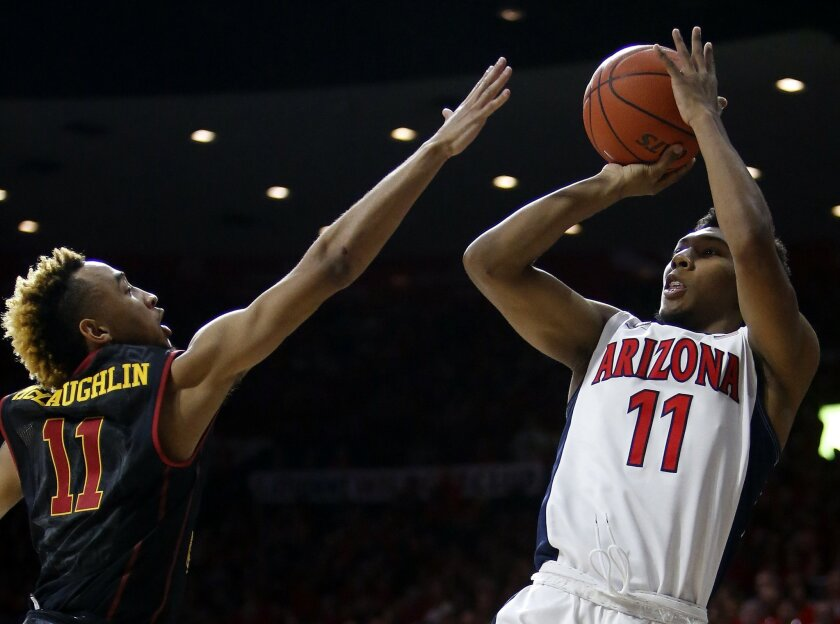 Arizona guard Allonzo Trier, right, shoots on Southern California guard Jordan McLaughlin during the second half of an NCAA college basketball game, Sunday, Feb. 14, 2016, in Tucson, Ariz. Arizona defeated Southern California 86-80. (AP Photo/Rick Scuteri)