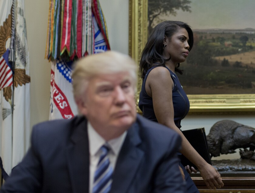 Omarosa Manigault walks past President Trump during a meeting in the Roosevelt Room of the White House last March.