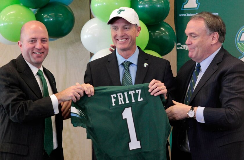 Tulane's athletics director, Troy Dannen, and President, Michael Fitz, present their new football coach, Willie Fritz, with his own Tulane jersey and hat during a news conference at Tulane University in New Orleans on Tuesday, Dec. 15, 2015. (Sherri Miller/The Advocate via AP)   MAGS OUT; INTERNET
