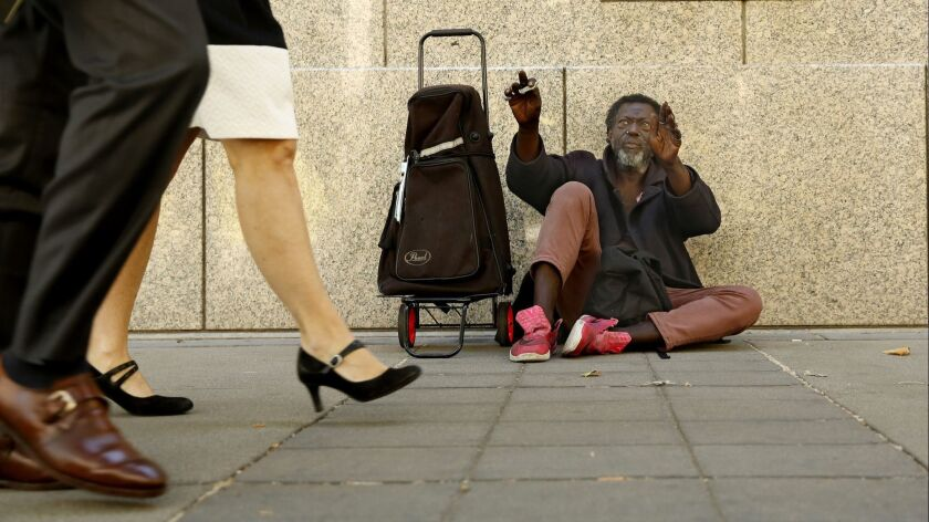 Carl Wallace, who says he is homeless and lives on the streets, waves to people passing by in Sacramento on Wednesday. The latest point-in-time count shows the number of people who are homeless in Sacramento County increased by 19% over the last two years.