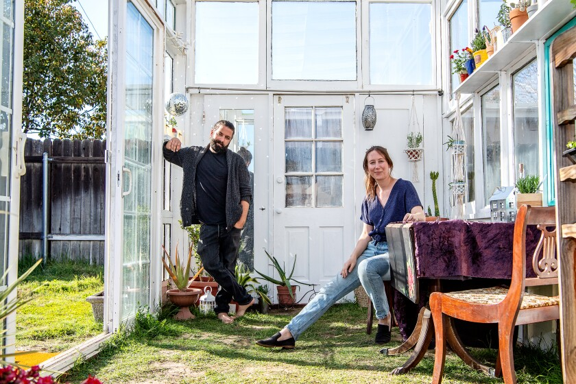 Trevor Morris stands in the greenhouse and Jenny Grosso sits at the greenhouse's dining table.