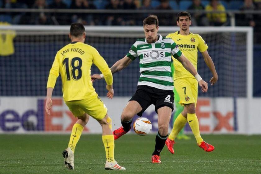 El centrocampista del Villarreal Javi Fuego (i) pelea un balón con el defensa uruguayo del Sporting de Portugal Sebastián Coates durante el partido de vuelta de dieciseisavos de final de la Liga Europa que se disputa en el estadio de la Cerámica. EFE