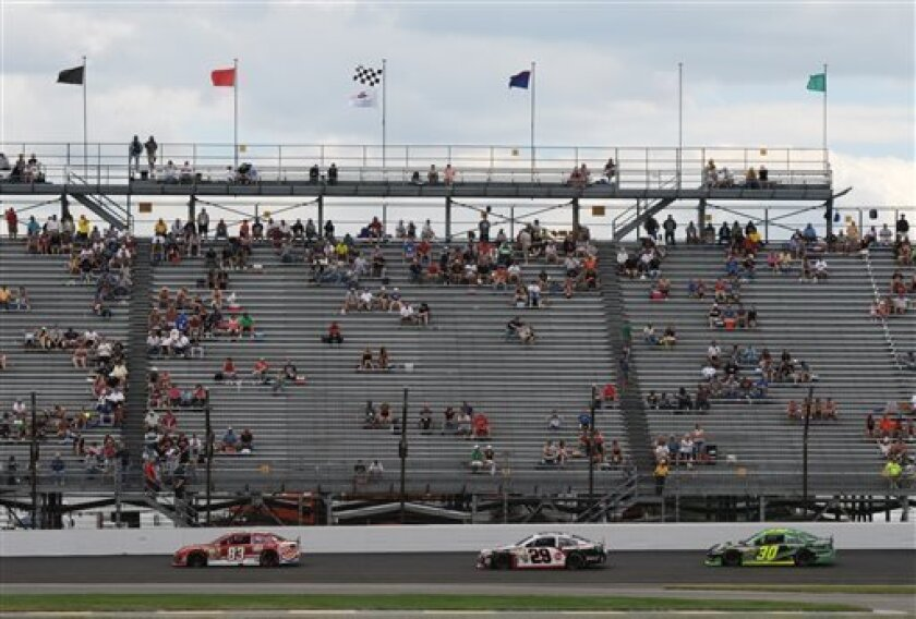 Sprint Cup Series driver David Reutimann (83), Kevin Harvick (29) and David Stremme (30) steer their cars during the Brickyard 400 auto race at the Indianapolis Motor Speedway in Indianapolis, Sunday, July 28, 2013. (AP Photo/Doug McSchooler)