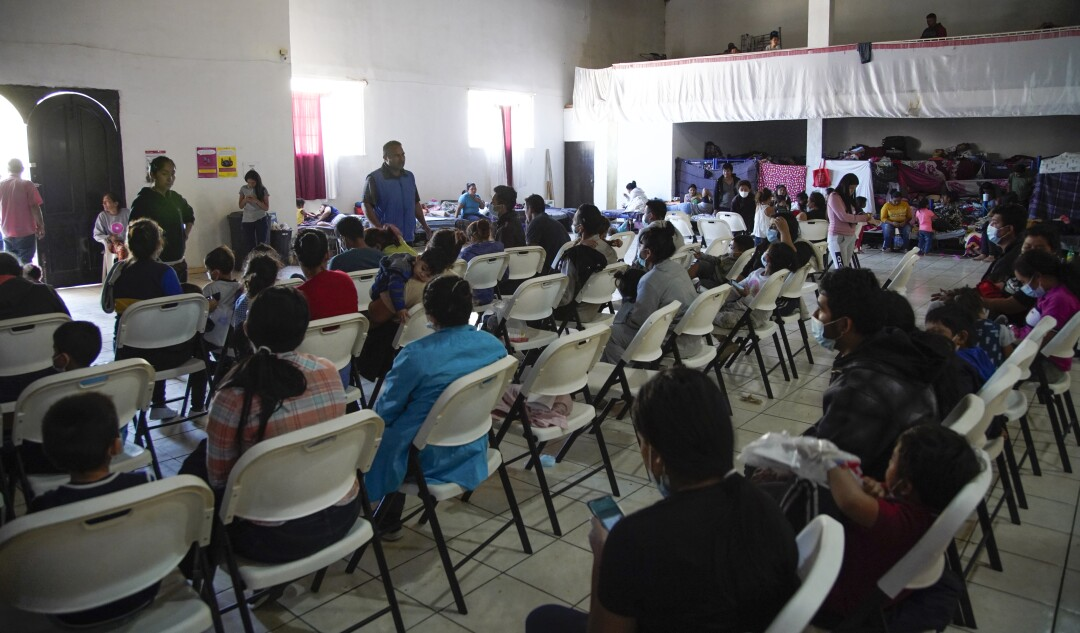 Asylum seekers seated in rows of chairs at Tijuana shelter