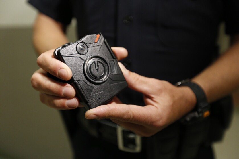 A Los Angeles police officers demonstrates how body cameras work in August 2015. Cameras in four LAPD divisions captured nearly 255,000 videos between August and December 2015, according to a new report from the department. (Al Seib / Los Angeles Times)