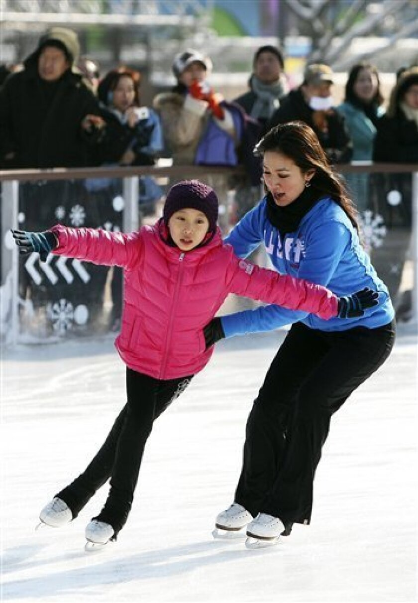 U.S. figure skater Michelle Kwan, a goodwill ambassador of the U.S. Department of State, right, holds an unidentified young South Korean figure skaters with developmental disabilities in a training session at Gwanghwamun Plaza Ice Skating Rink in Seoul, South Korea, Tuesday, Jan. 5, 2009. Kwan called South Korea's Kim Yu-na an influential role model for future champions from the Asian nation.(AP Photo/Yonhap, Kim Hyun-tae)