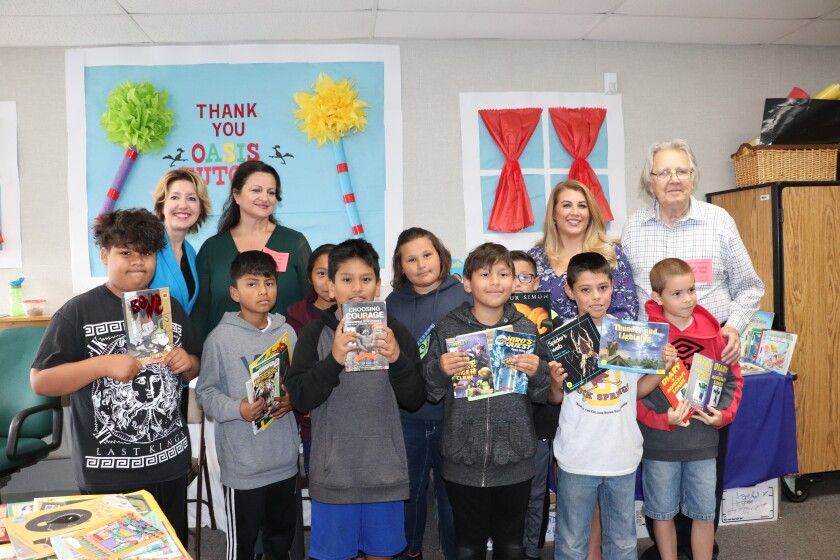 Rock Springs elementary fourth-graders received free books from the Oasis literacy tutoring program. Back row: Simona Valanciute, San Diego Oasis; Svetlana Larkin, The Charitable Foundation; Sara Vaz, Nordson Corporation Foundation; and John Dunnicliff, San Diego Oasis.