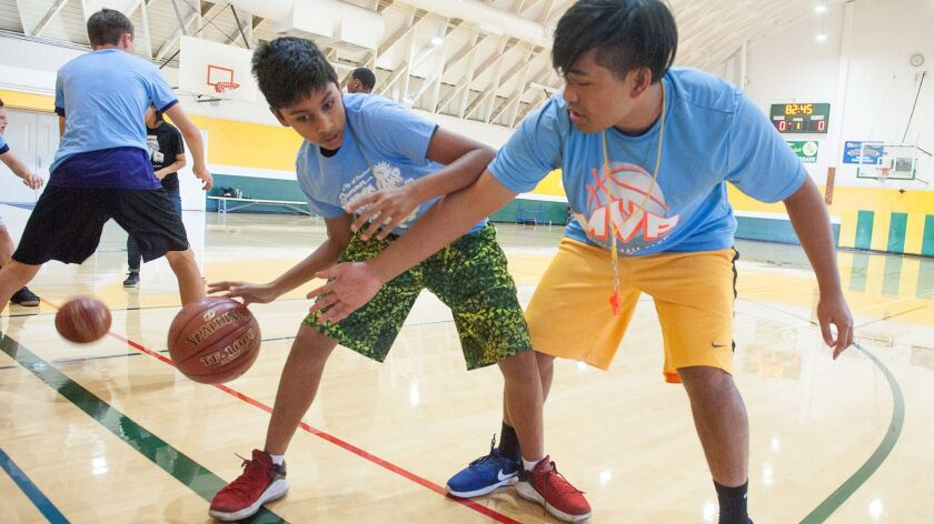 Jeremy Jitendra, left, protects the ball from volunteer coach Loranzo Antonio during the MVP Summer