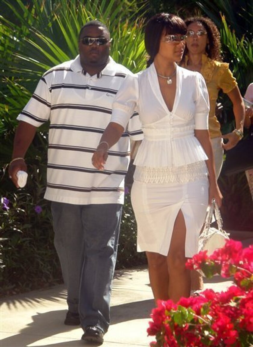 U.S. actress LisaRaye McCoy, the estranged wife of Turks and Caicos' Prime Minister Michael Misick, arrives with her bodyguard Phillip Travis, left, to a commission investigating corruption allegations against Misick, in Providenciales, Turks and Caicos, Friday, Jan. 30, 2009. The embattled premier of the island chain nation south of the Bahamas has denied granting special immigration status to a developer in exchange for a $6 million loan. (AP Photo/Turks and Caicos Sun)