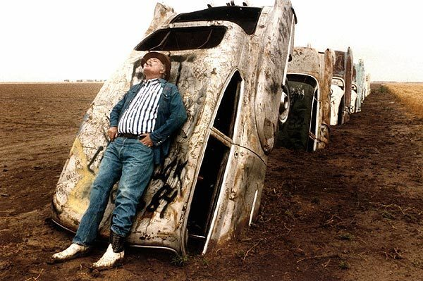 Stanley Marsh III leans on one of 10 Cadillacs buried on his ranch west of Amarillo, Texas, along old Route 66, in this June 1984 photo.